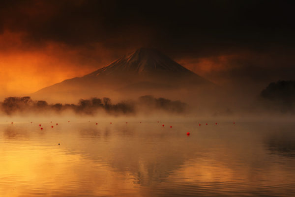 Landscape of mountain Fujisan or Mount Fuji at sunrise with dark cloud and mist from Lake Shoji or Shojiko with reflection on water in Yamanashi Prefecture, Japan.