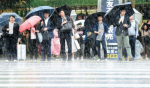 People holding umbrellas in rain at train station entrance in Japan