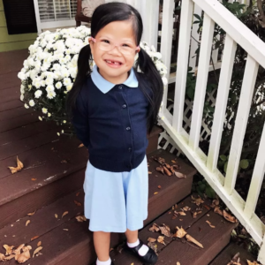 Rosie in school uniform preparing to go to school, abandoned Chinese girl with Down Syndrome adopted by American family